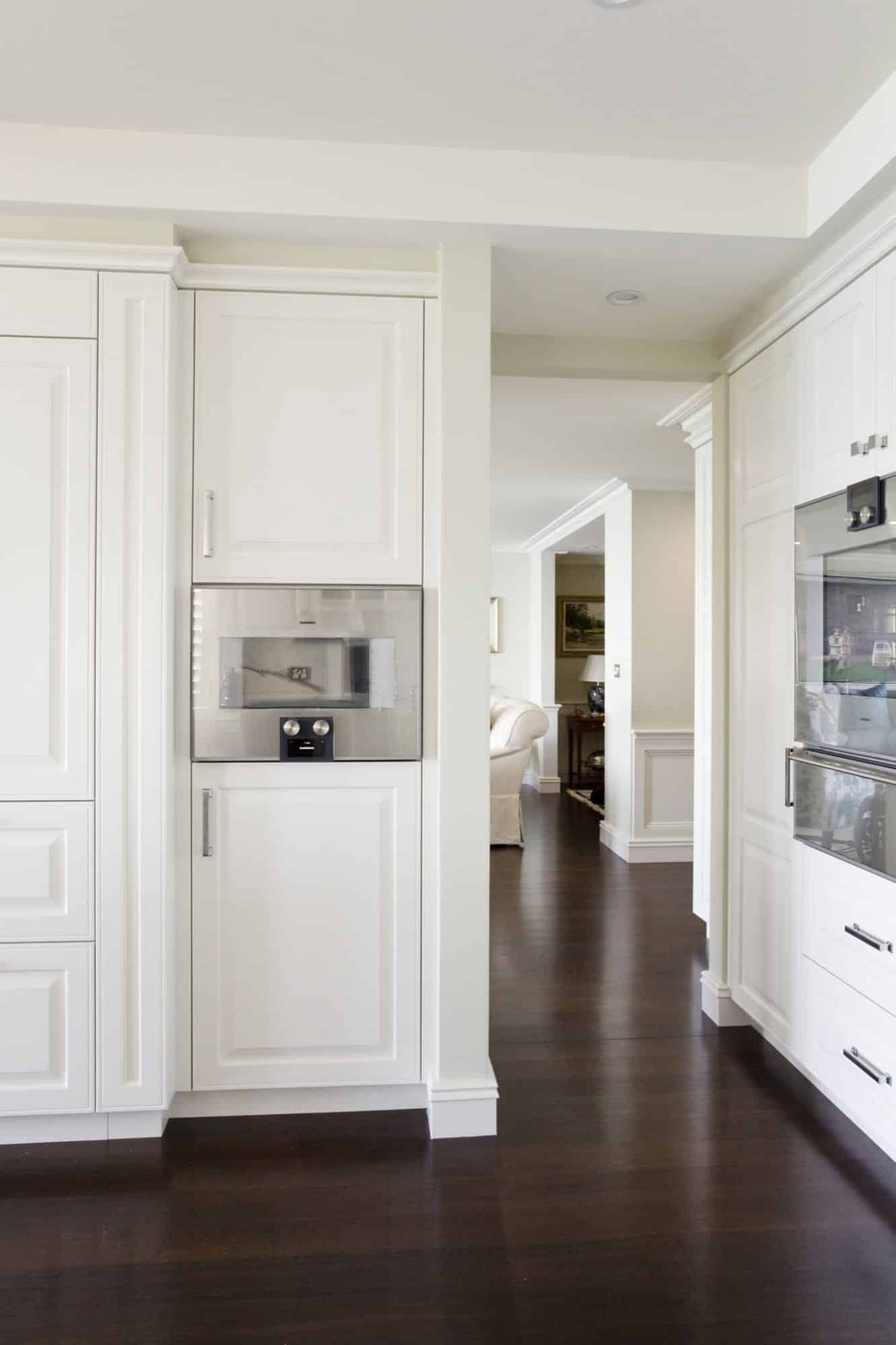 Detailed kitchen joinery in white paired with dark timber floors